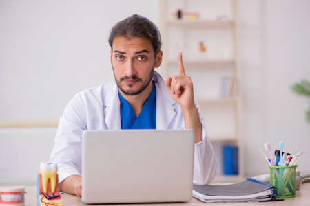 Young male odontologist in telemedicine concept