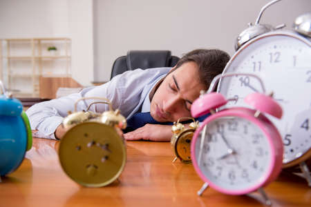 Young male employee sleeping in the office in time management co