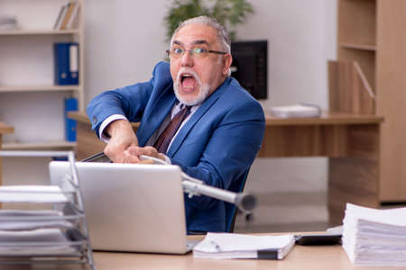 Old businessman employee after accident working in the office