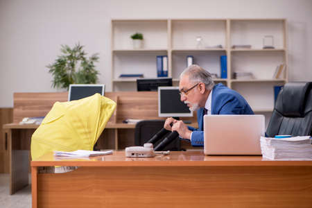 Aged businessman employee looking after newborn at workplace