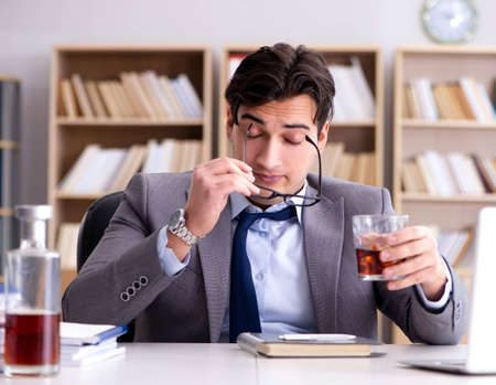 Young businessman drinking from stress Reklamní fotografie