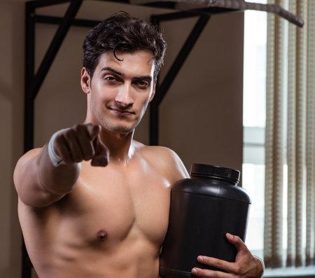 Man with nutrient supplements in sports gym Reklamní fotografie