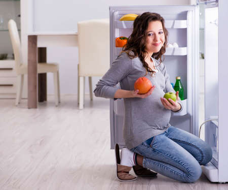 Pregnant woman near fridge looking for food and snacks Reklamní fotografie