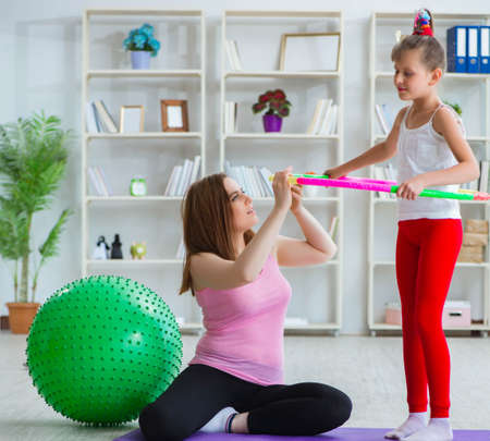 Girl and mother exercising at home Reklamní fotografie