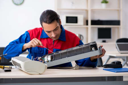 Young repairman repairing air-conditioner at warranty center Stock Photo