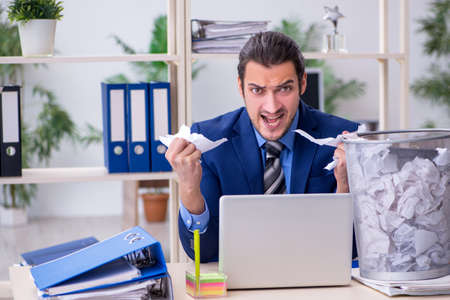 Young businessman employee rejecting new ideas with lots of pape