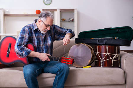 Senior male repairman repairing musical instruments at home