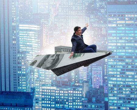 Businessman flying on paper plane in business concept Banco de Imagens