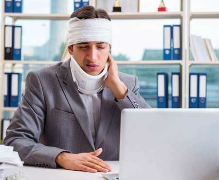 Injured businessman working in the office Stock Photo