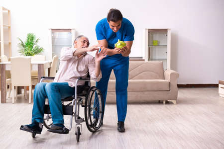 Old man in wheel-chair and young bad caregiver indoors Foto de archivo