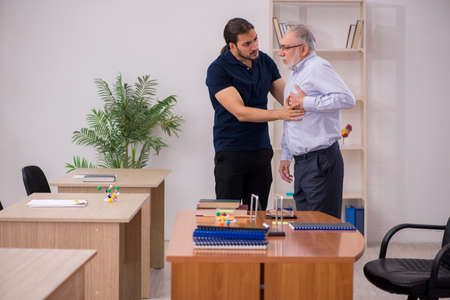 Old male teacher feeling bad during individual lesson Stock Photo