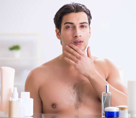 Young man is getting prepared for working day in bathroom