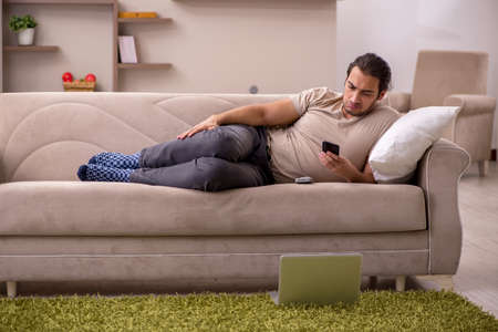 Young man lying on the sofa at home