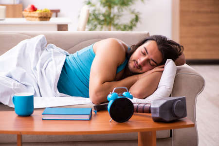 Young man lying on the sofa in time management concept