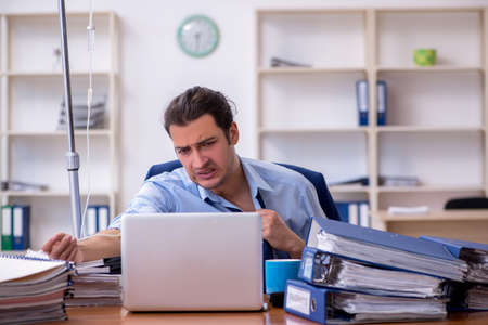 Young male employee suffering at workplace Stock Photo