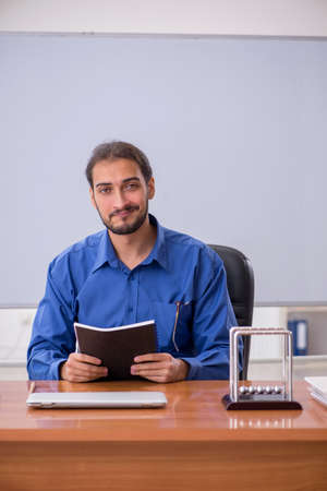 Young male teacher physicist sitting in the classroom Archivio Fotografico
