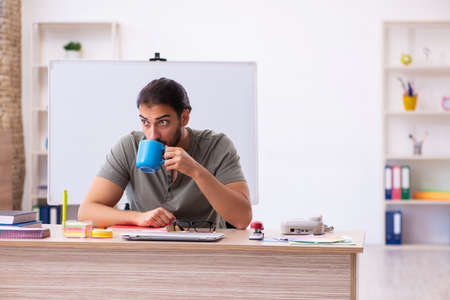 Young male designer drinking coffee in the office