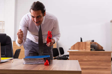 Young male employee with dynamite in the office Imagens