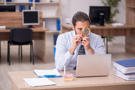 Young businessman employee holding loupe in auditing concept