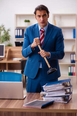 Young male employee holding plunger in funny concept Banque d'images