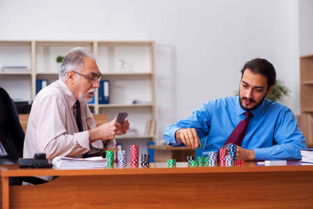 Two male employees playing cards at workplace