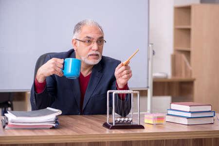 Old teacher physicist sitting in the classroom Archivio Fotografico