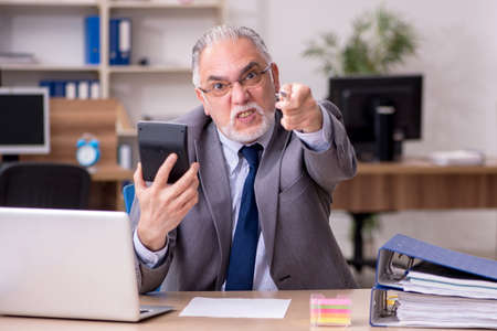 Old male employee working in the office Imagens