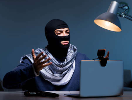 Hacker wearing balaclava mask hacking computer