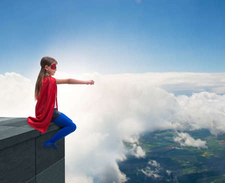Young girl in superhero costume overlooking the city