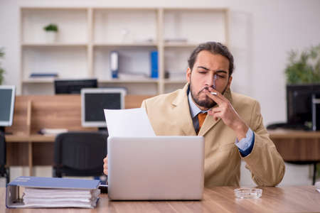 Ill cigarette addicted male employee working in the office