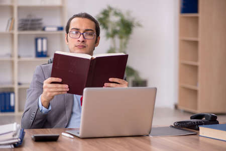 Young male employee student reading book at workplace