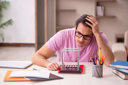 Young male student physicist preparing for exam at home