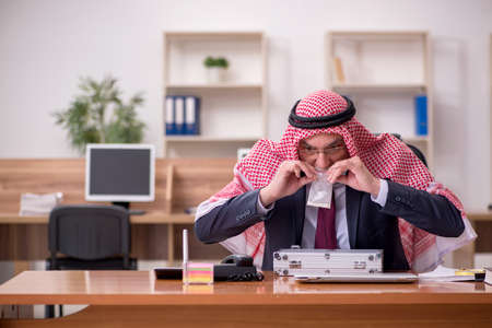 Aged arab businessman selling narcotics at workplace