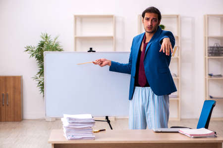Young male employee in oversleeping concept in front of whiteboard
