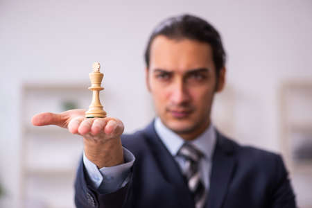 Young male employee playing chess at workplace