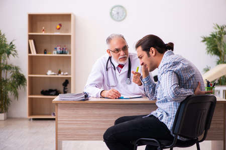 Young male patient visiting aged male doctor