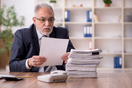 Aged male employee sitting at workplace Stock Photo