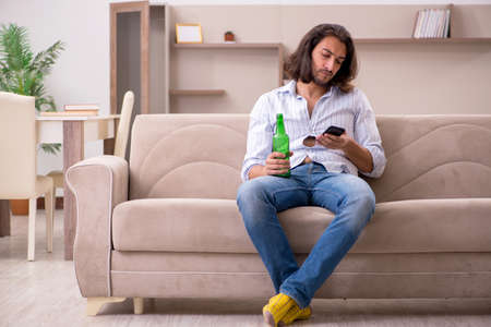 Young man drinking alcohol at home