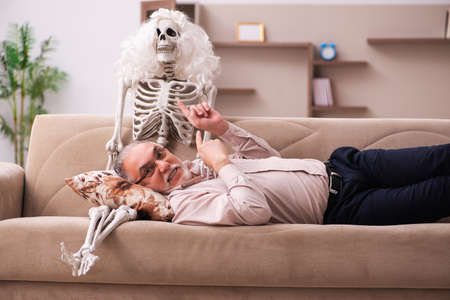Old man sitting on the sofa with the female skeleton