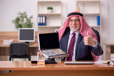 Aged arab businessman employee holding case with banknotes in th