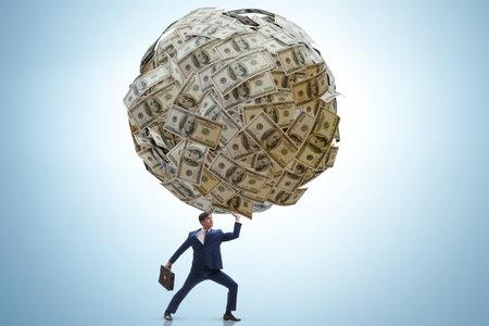 Businessman with heavy dollar ball