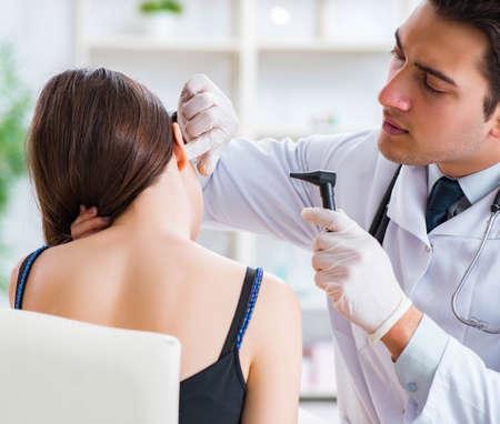 Doctor checking patients ear during medical examination Foto de archivo