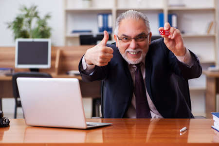 Old male employee in gambling concept at workplace Standard-Bild
