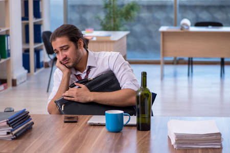 Young male alcohol addicted employee working in the office Standard-Bild