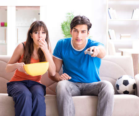 Young man watching football with his wife at home Stock Photo