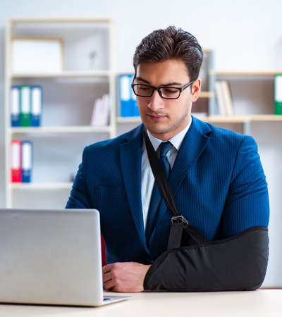 Businessman with broken arm working in office Stock Photo