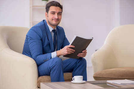 Young male employee waiting for business meeting