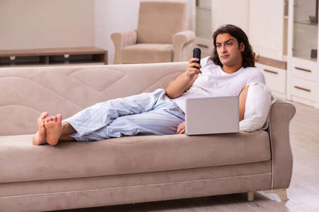 Young lazy man in oversleeping concept at home