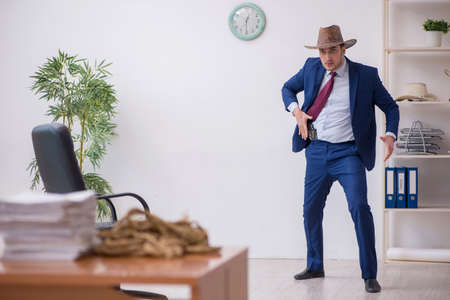 Young cowboy businessman working at workplace
