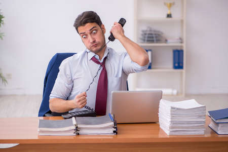 Young businessman and too much work in the office Foto de archivo